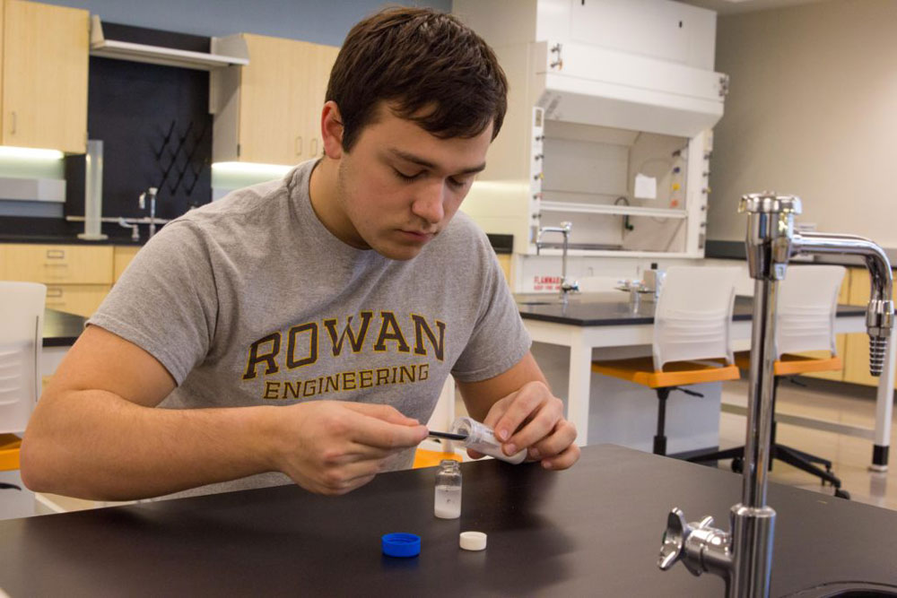 A male student in a Rowan engineering shirt works with a beaker